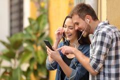 Het gelukkige paar lachen die aan muziek online luisteren stock foto