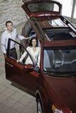 Het gelukkige paar in luxeauto toont ruimte Stock Afbeelding