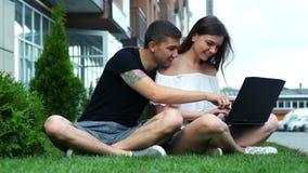 Het gelukkige paar maakt online aankopen gebruikend laptop, kiest goederen, zittend op het gras stock videobeelden