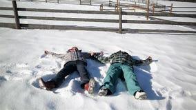 Het gelukkige Paar maakt Sneeuw Angel Lying samen ter plaatse tijdens Sunny Warm Day De man en de vrouw hebben pret stock videobeelden