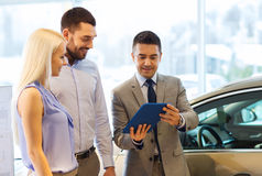 Het gelukkige paar met autohandelaar in auto toont of salon Stock Afbeeldingen