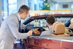 Het gelukkige paar met autohandelaar in auto toont of salon Royalty-vrije Stock Fotografie