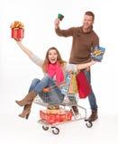 Het gelukkige paar met boodschappenwagentje van Kerstmis stelt voor Royalty-vrije Stock Afbeeldingen