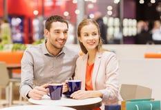 Het gelukkige paar met het winkelen doet het drinken koffie in zakken Stock Foto's