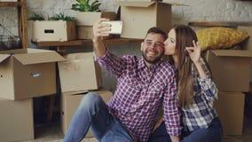 Het gelukkige paar neemt selfie met huissleutels na het kopen van nieuwe flat De jongeren stelt en kust stock footage
