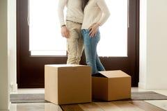 Het gelukkige paar omhelzen die zich dichtbij dozen bij het bewegen van dag bevinden, sluit stock afbeelding