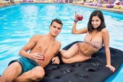 Het gelukkige paar ontspannen met cocktails op een blauwe opblaasbare matras bij het zwembad Stock Foto
