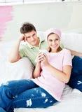 Het gelukkige paar ontspannen na het schilderen van een ruimte Stock Afbeeldingen