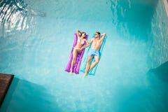 Het gelukkige paar ontspannen op opblaasbaar vlot bij zwembad Royalty-vrije Stock Foto's