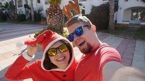 Het gelukkige paar in santahoeden die selfie beeld nemen van dient in openlucht de zomer in stock video