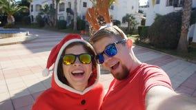 Het gelukkige paar in santahoeden die selfie beeld nemen van dient in openlucht de zomer in stock footage