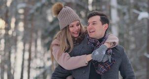 Het gelukkige Paar speelt de Winterspel buiten het Genieten van van Zonlicht en Warm de Winterweer in de Bergen De sterke Jongen  stock videobeelden