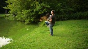 Het gelukkige paar speelt samen buiten het genieten van het besteden tijd in het park De sterke jongen wervelt in openlucht zijn  stock video