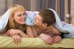 Het gelukkige paar spelen in het bed Royalty-vrije Stock Afbeeldingen