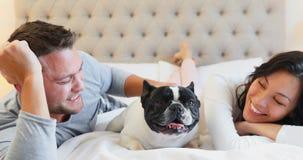 Het gelukkige paar spelen met pug hond 4k stock footage