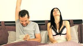 Het gelukkige paar spelen met tablet en telefoon in bed stock video