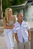 Het gelukkige paar stellen door de pool Stock Fotografie