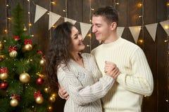 Het gelukkige paar stellen in Kerstmisdecoratie, donker houten binnenland met lichten Romantisch avond en liefdeconcept De vakant royalty-vrije stock foto's