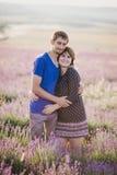 Het gelukkige paar stellen op een lavendelgebied Stock Fotografie