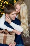 Het gelukkige paar van minnaars in truien geeft elkaar giften Stock Foto's