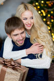 Het gelukkige paar van minnaars in truien geeft elkaar giften Stock Afbeelding