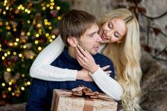 Het gelukkige paar van minnaars in truien geeft elkaar giften Stock Foto