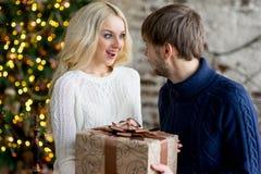 Het gelukkige paar van minnaars in truien geeft elkaar giften Stock Fotografie