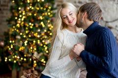 Het gelukkige paar van minnaars in truien geeft elkaar giften Stock Afbeeldingen