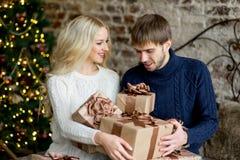 Het gelukkige paar van minnaars in truien geeft elkaar giften Royalty-vrije Stock Fotografie