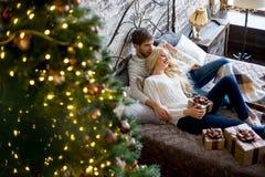 Het gelukkige paar van minnaars in witte sweaters geeft elkaar giften Royalty-vrije Stock Foto