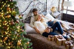 Het gelukkige paar van minnaars in witte sweaters geeft elkaar giften Royalty-vrije Stock Fotografie