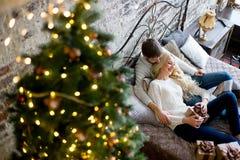 Het gelukkige paar van minnaars in witte sweaters geeft elkaar giften Royalty-vrije Stock Foto's