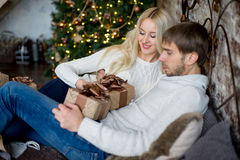 Het gelukkige paar van minnaars in witte sweaters geeft elkaar giften Stock Foto