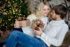 Het gelukkige paar van minnaars in witte sweaters geeft elkaar giften Stock Afbeelding