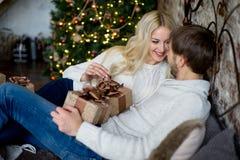 Het gelukkige paar van minnaars in witte sweaters geeft elkaar giften Royalty-vrije Stock Afbeeldingen