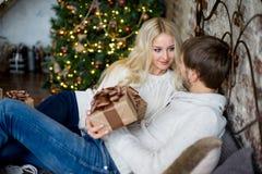 Het gelukkige paar van minnaars in witte sweaters geeft elkaar giften Royalty-vrije Stock Afbeelding