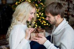 Het gelukkige paar van minnaars in witte truien geeft elkaar giften Stock Fotografie