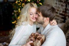 Het gelukkige paar van minnaars in witte truien geeft elkaar giften Royalty-vrije Stock Fotografie