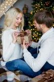 Het gelukkige paar van minnaars in witte truien geeft elkaar giften Stock Foto