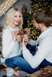Het gelukkige paar van minnaars in witte truien geeft elkaar giften Royalty-vrije Stock Foto's