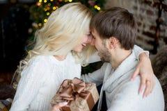 Het gelukkige paar van minnaars in witte truien geeft elkaar giften Stock Afbeelding