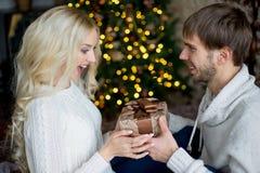 Het gelukkige paar van minnaars in witte truien geeft elkaar giften Royalty-vrije Stock Afbeelding