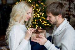 Het gelukkige paar van minnaars in witte truien geeft elkaar giften Royalty-vrije Stock Afbeeldingen