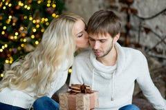 Het gelukkige paar van minnaars in witte truien geeft elkaar giften Stock Foto's