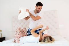 Het gelukkige paar vechten met hoofdkussens in bed royalty-vrije stock foto's