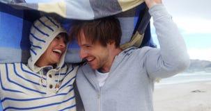 Het gelukkige paar verbergen in deken bij strand stock footage