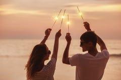Het gelukkige paar viert zonsondergang met sterretjes royalty-vrije stock fotografie