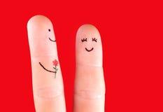 Het gelukkige paarconcept - een man met bloem en een vrouw, schilderde bij Stock Foto's