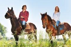 Het gelukkige paarhorseback berijden in bloemrijke weiden Royalty-vrije Stock Foto