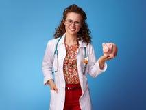 Het gelukkige pediater spaarvarken van de artsenholding op blauw royalty-vrije stock afbeeldingen
